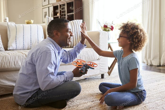Girl sitting cross legged on the floor of the sitting room giving a high five to her grandfather