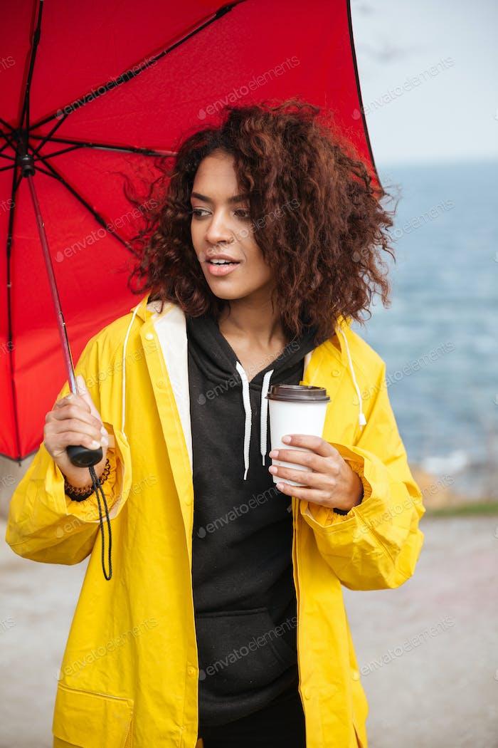 Konzentrierte afrikanische lockige junge Dame zu Fuß im Freien und trinken Kaffee.