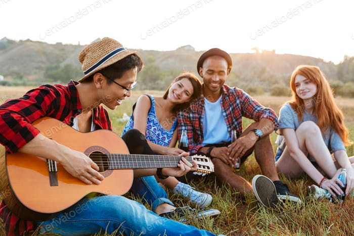 Happy relaxed young people drinking beer and playing guitar outdoors
