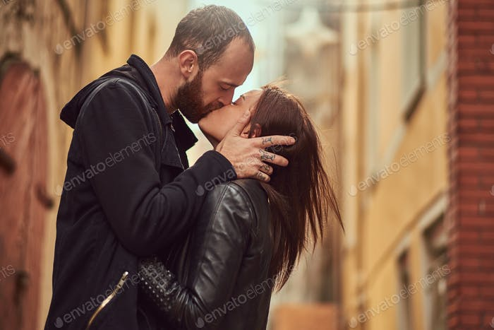 Bearded man and brunette girl kissing, on the background of the old European street.