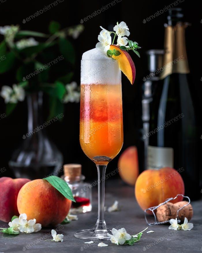 Layered Bellini Cocktail mit Pfirsiche auf dunklem Hintergrund