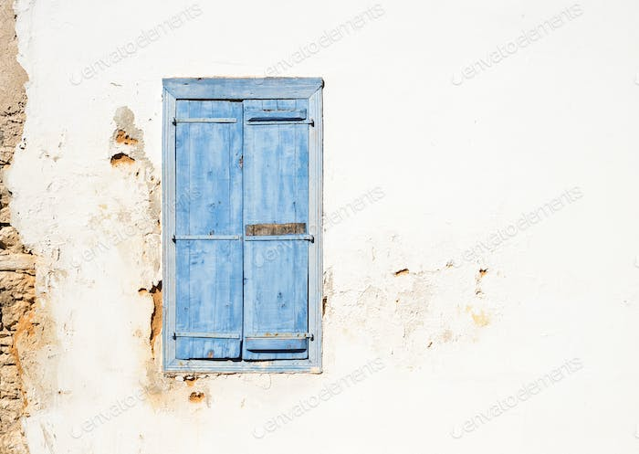Mediterranean style old window. Blue on light wall with closed shutters.