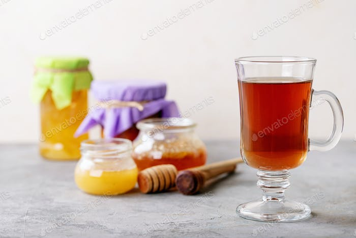 Glass cup of black tea served with honey