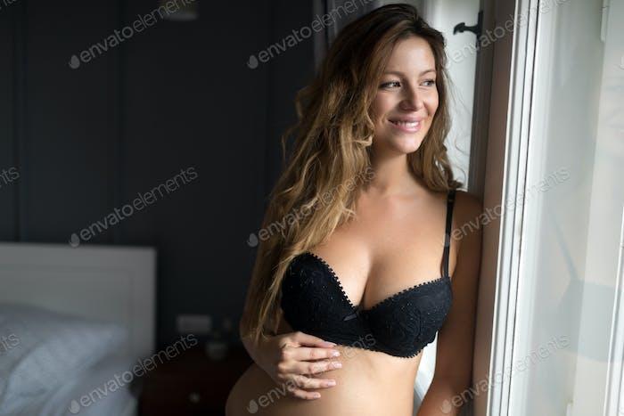 Fashion photo of beautiful pregnant girl posing in sexy black lingeri