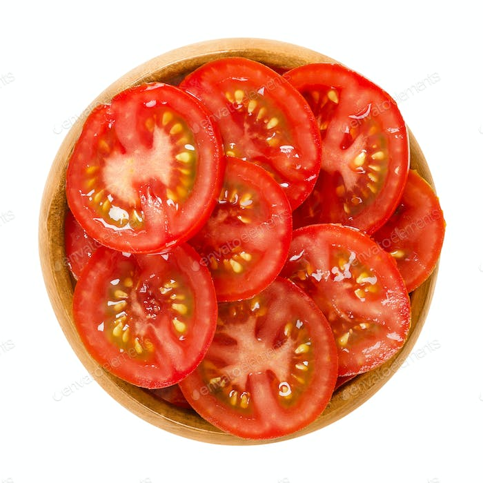 Tomato slices in wooden bowl over white