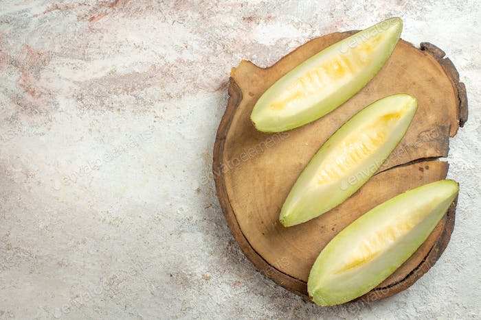 slices of melon on wooden platter on the right side of marble background