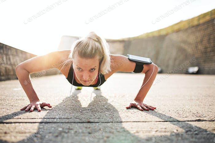 Young sporty woman runner with smartphone doing push-ups outside.