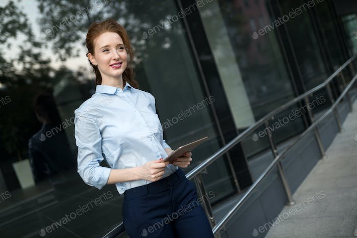 Portrait of businesswoman walking and holding tablet