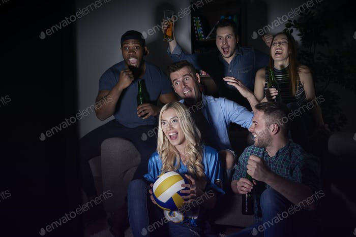 Boys and girls watching match at night