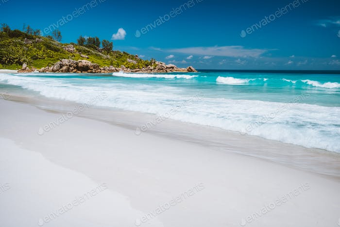 Vacation holiday. Rolling ocean waves, pristine blue color lagoon and granite rocks on Anse Coco