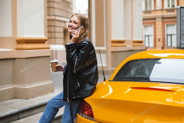 Pretty cheerful girl in leather jacket with cup of coffee to go