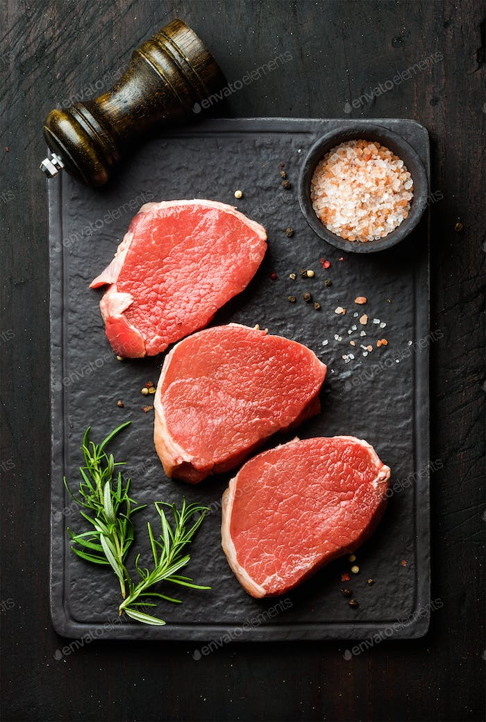Raw beef Eye Round steaks with spices and rosemary