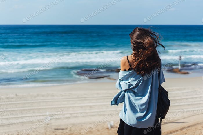 Young beautiful girl looks afar at sea