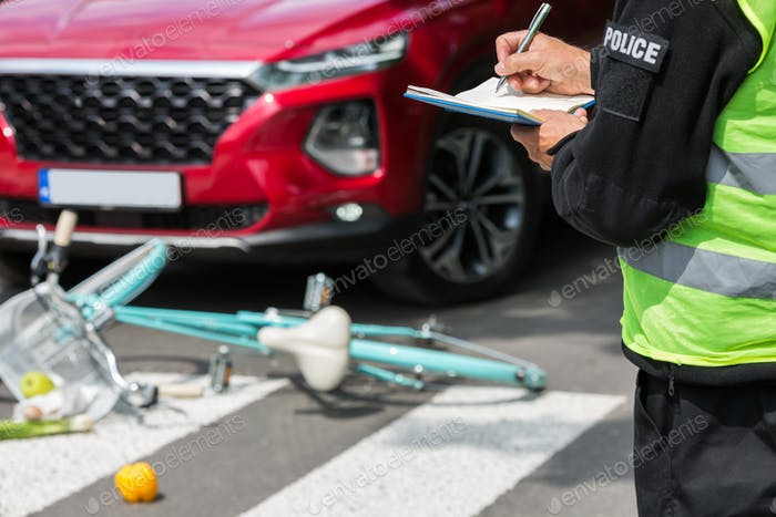 Policeman writes a ticket standing in front of a red car that hit a cyclist on a pedestrian lane