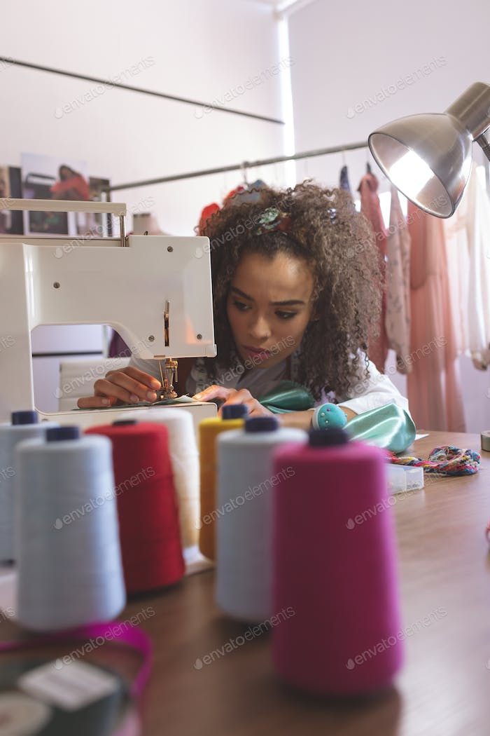 Front view of young Mixed-race female fashion designer working with sewing machine