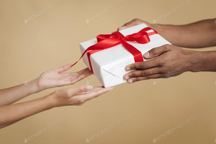 Happy New Year celebration holiday on party. Hands of african american man give box with gift