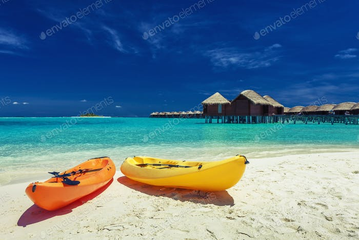 Yellow and orangel kayaks on the tropical beach with villas