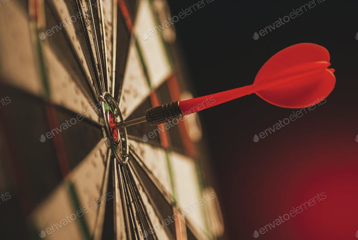 Successful bulls eye centre dart on a target