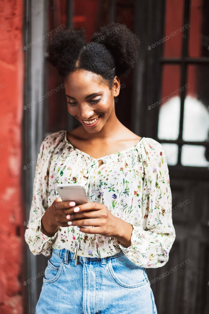Beautiful smiling girl in blouse happily using cellphone outdoor