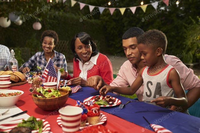 Multi generation black family members at a 4th July barbecue