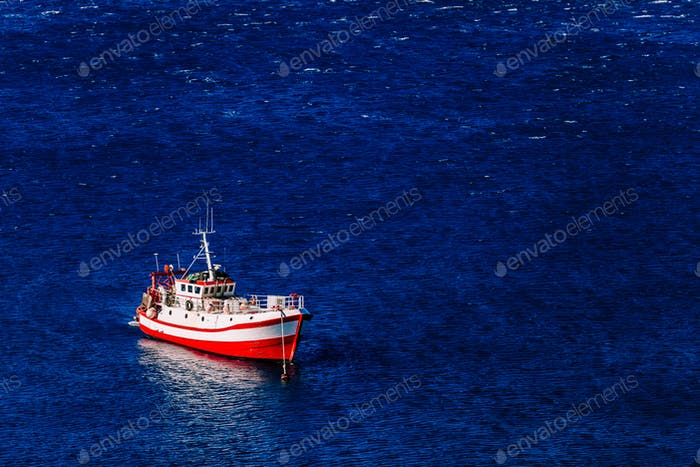 Aerial view of red fishing boat on a deep blue sea in Greece.