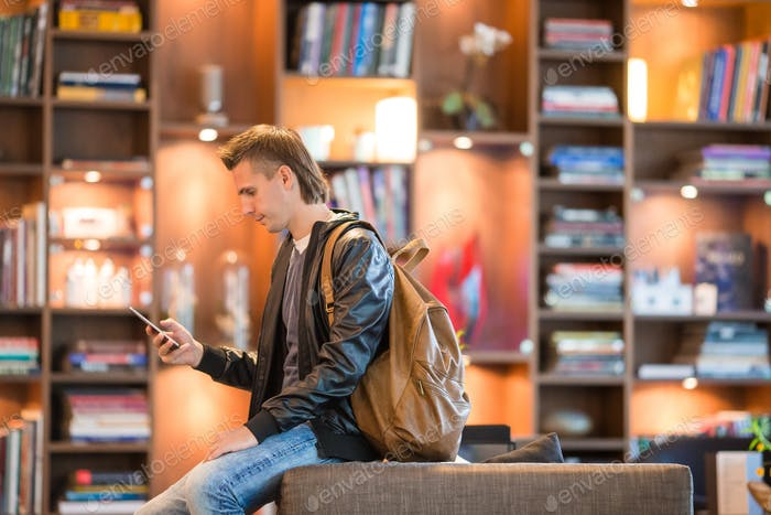 Young positive man picking new book on shelves in bookstore