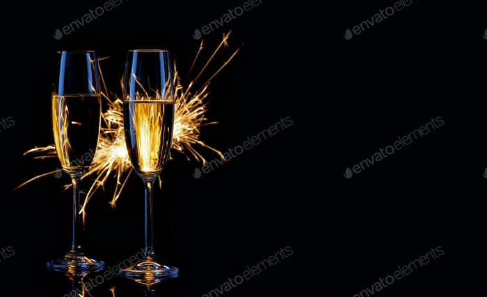 Two glasses of champagne and sparklers on black background