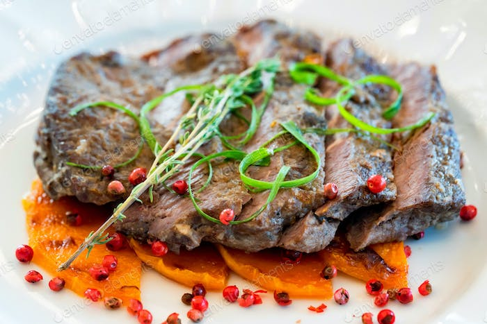 Sliced beef with pumpkin served on white plate
