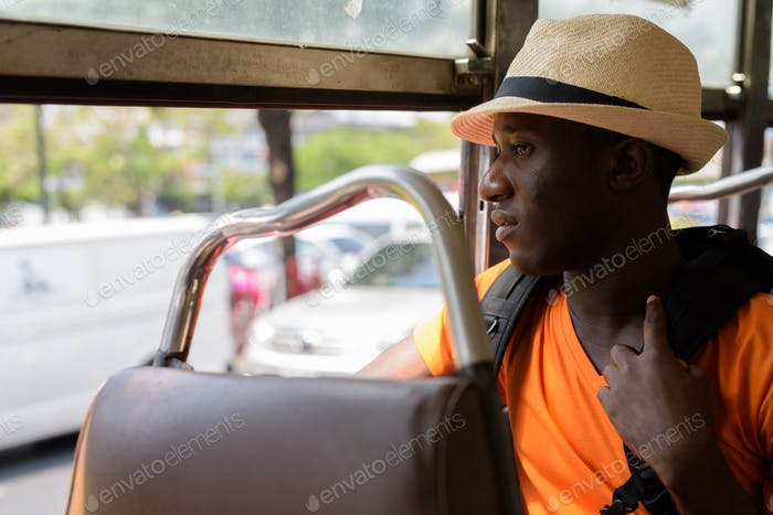 Profile view of young black African tourist man in bus