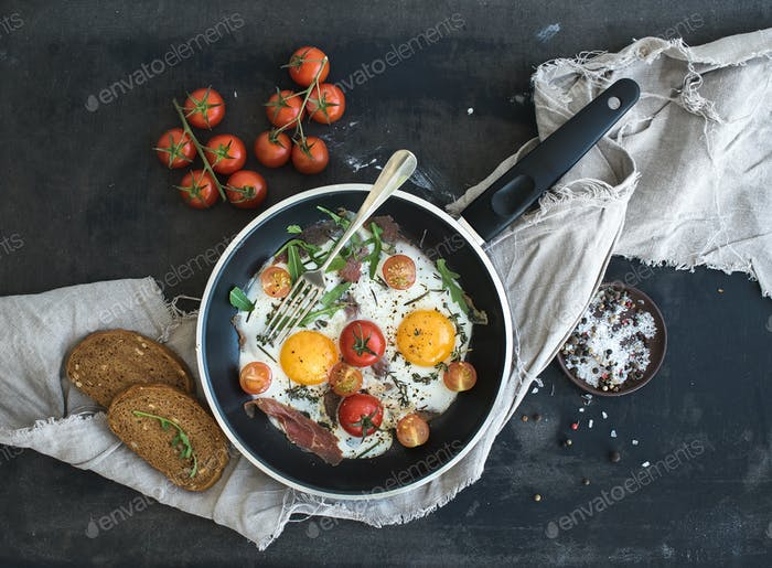 Pan of fried eggs, bacon and cherry-tomatoes with bread on dark table surface