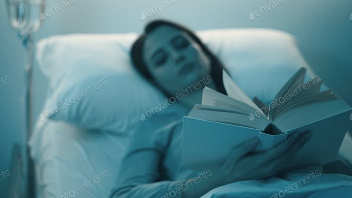 Young sleepless patient lying in the hospital bed and reading a book