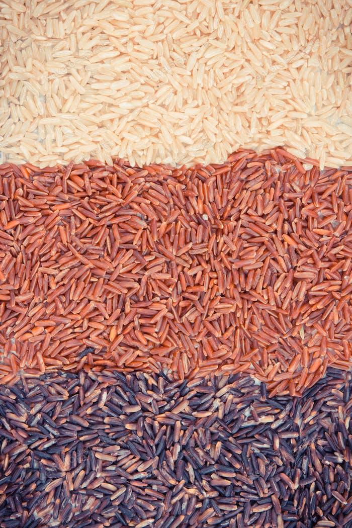 Vintage Foto, Brauner, schwarzer und roter Reis als Hintergrund, gesundes glutenfreies Lebensmittelkonzept