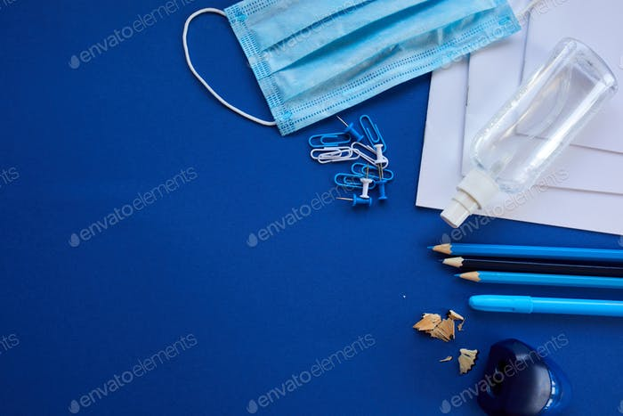 School supplies, protective mask and antiseptic on a blue background