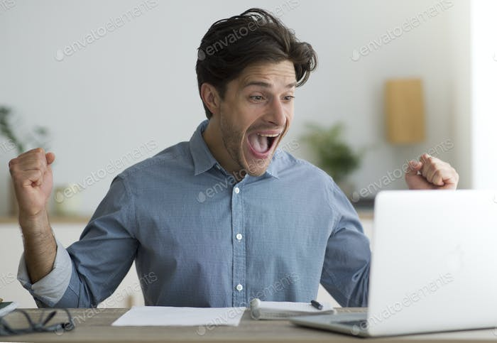 Guy Celebrating Success At Laptop Shaking Fists At Workplace