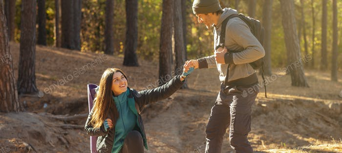 Cropped image of man supporting woman during hiking