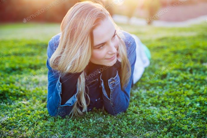Pretty girl lying down on green grass