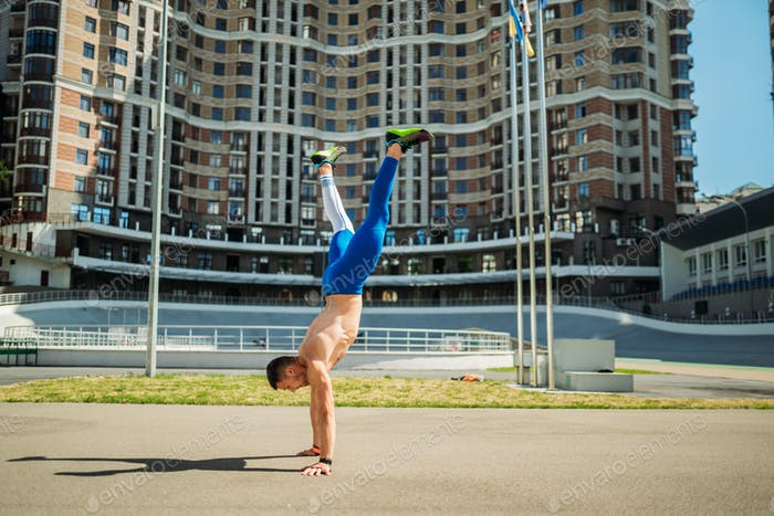 Muscular guy stands on his hands against a of a tall building
