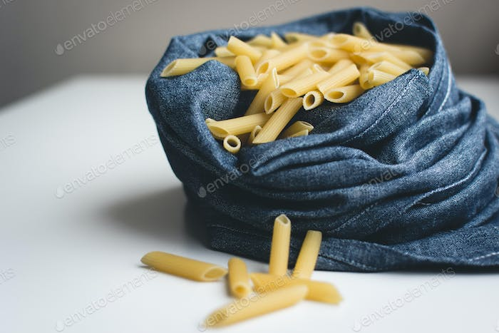 Detail of pasta penne in a blue linen