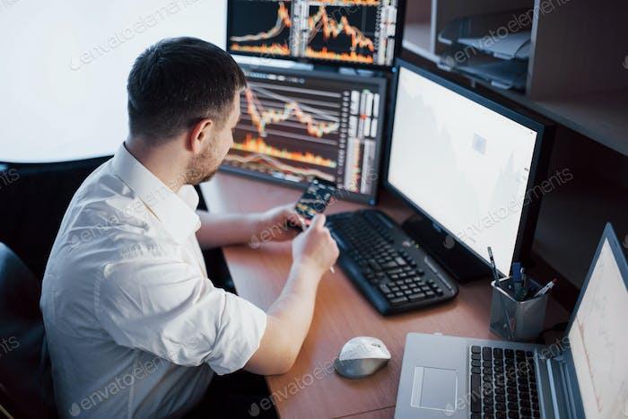 Einsatz moderner Technologien bei der Arbeit. Junger Geschäftsmann, der am digitalen Tablet arbeitet, während er an der