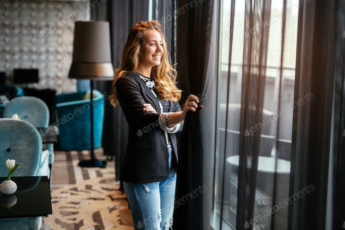 Glamorous woman staring through window