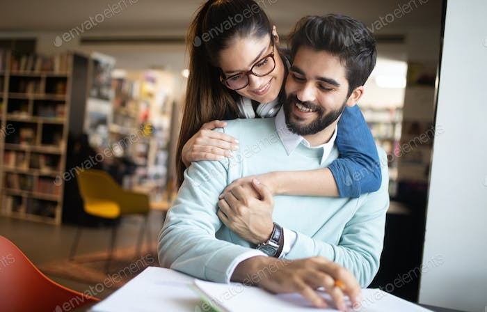 Young couple reading books and studying together in library