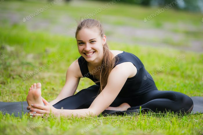 Woman stretching outdoors in a park before yoga practice