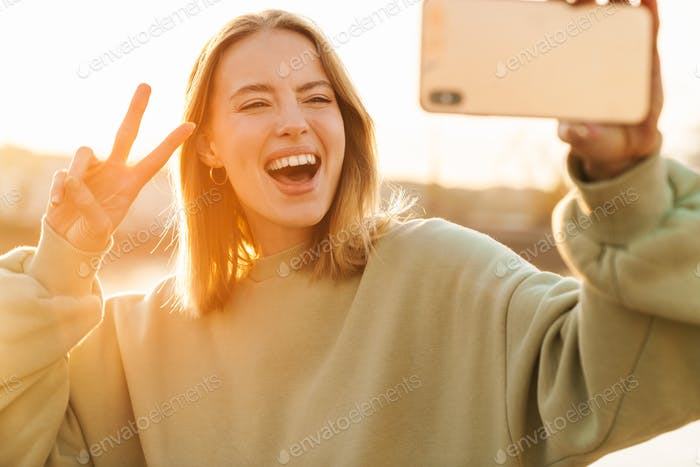 Portrait of woman gesturing peace sign and taking selfie on cellphone