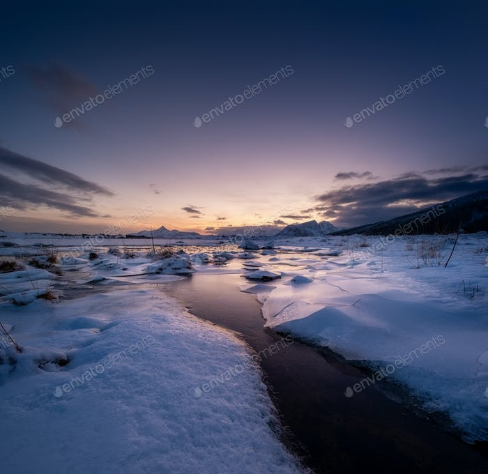 Lofoten islands, Norway. Mountains, ice with snow and clouds during sunset. Evening time.