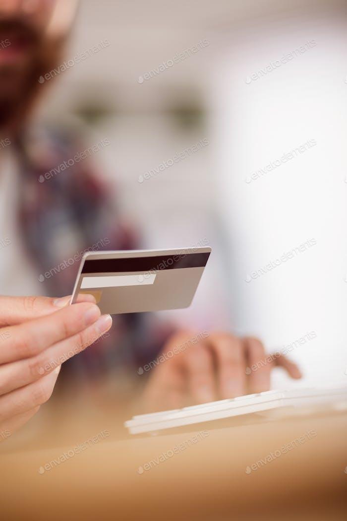 Hipster Geschäftsmann Shopping online mit Karte in seinem Büro