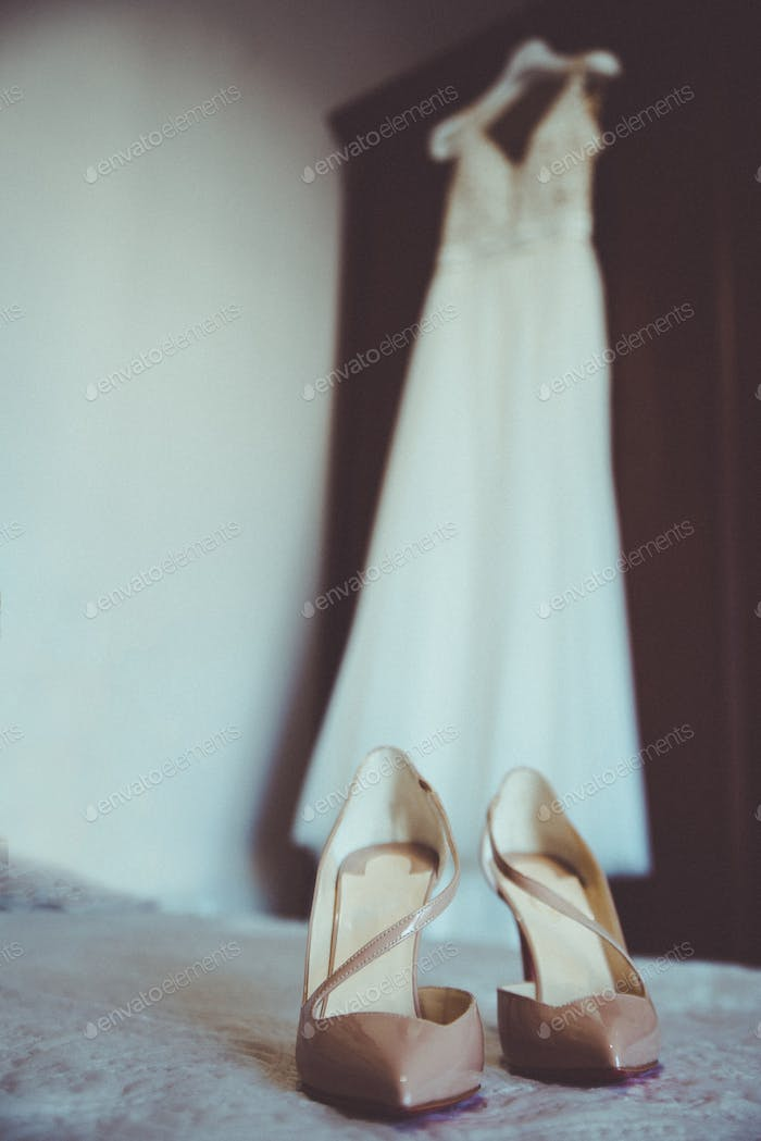 Wedding dress and wedding shoes on the bed.