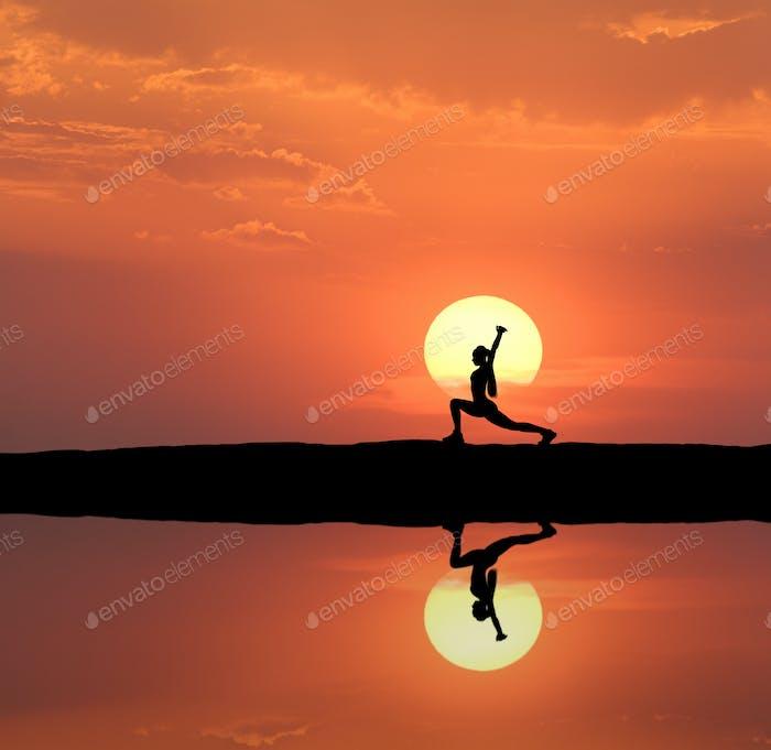 Silhouette einer stehenden sportliche Frau praktiziert Yoga
