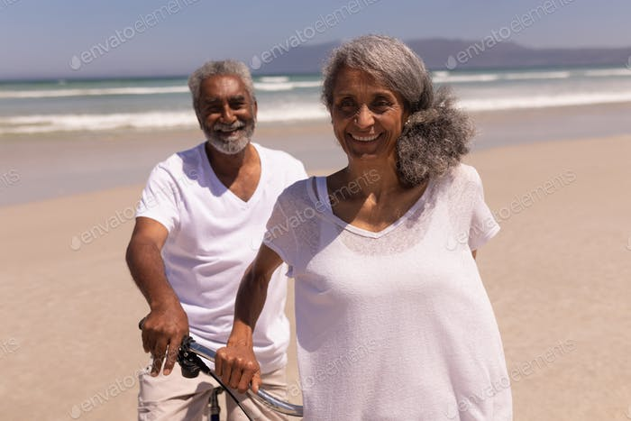 Senior couple standing with bicycle and looking at camera on beach in the sunshine with mountains