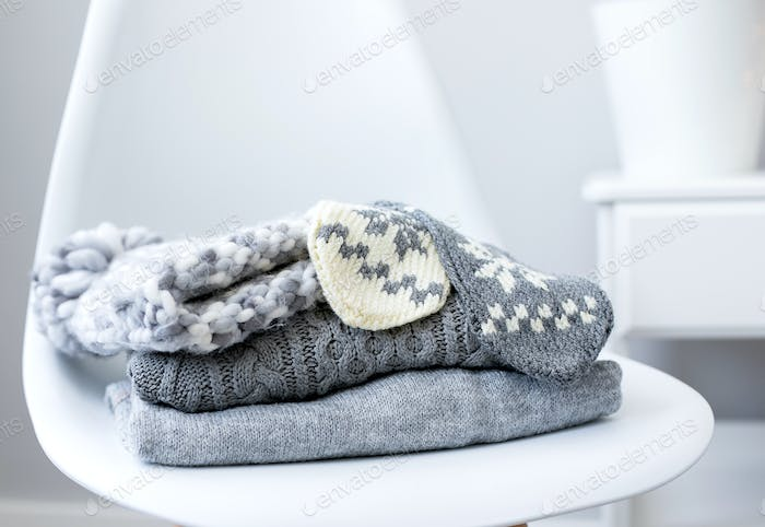 A stack of knitted sweaters and accessories on chair in Interior of the living room