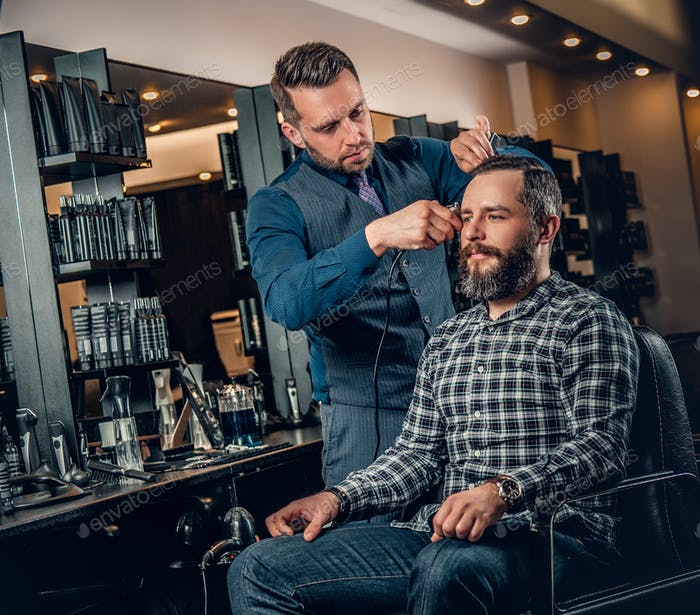 Stylish male hairdresser doing haircut to a bearded male in a sa